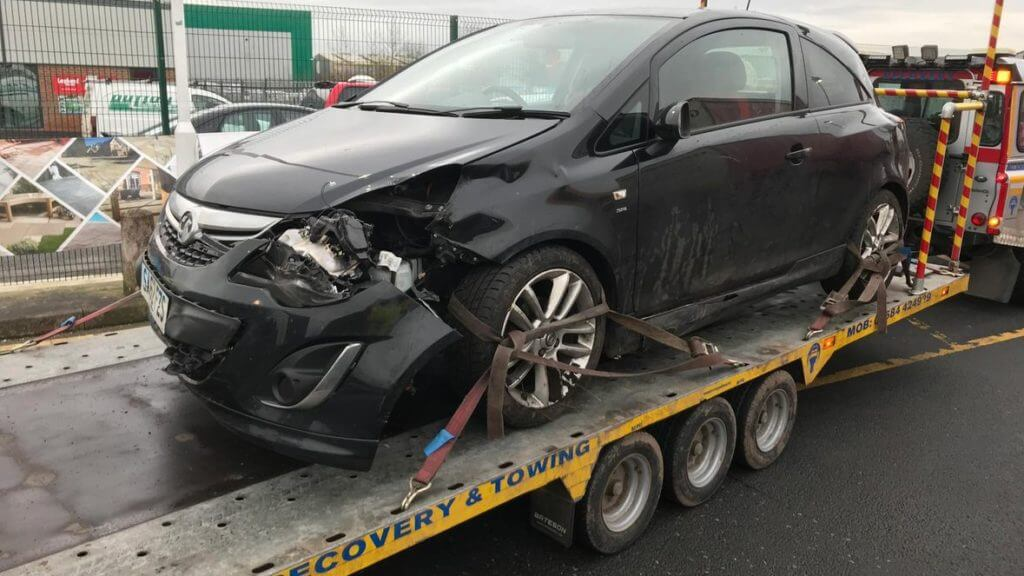 Accident-damaged car on transporter